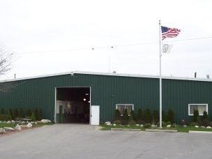 A large green metal building with a flag pole in front.